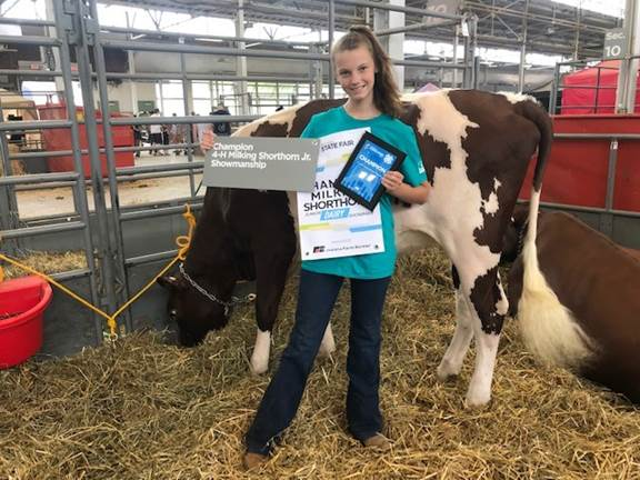 Photo: Emmie Haddon proudly displays her awards of champion 4-H milking shorthorn junior showmanship and third place in her milking shorthorn class at Indiana State Fair (courtesy photo).